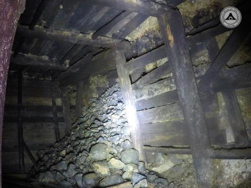 Trafione ! Widok w stronę wejścia do podziemi. Widać betonową ścianę przedzielającą sztolnie 1 i zabezpieczenie wyjścia ze śluzy gazowej. Fakt postawienia ściany świadczy o zakończeniu prac górniczych, niestety nie pozwala ona na zbadanie długości zasypanego chodnika wejściowego.