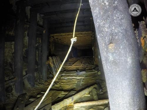 Widok w stronę wnętrza góry. Częściowo zdemontowane tory, wykorzystywane do zbrojenia ociosów i stropu, potwierdzają, że etap górniczy Niemcy zakończyli. Widoczne przewody elektryczne i ociosy wzmocnione szynami i betonem. W głębi po lewej stronie wejście do wartowni.